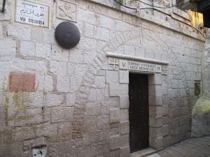 The fifth Station of the Cross on the Via Dolorosa (Way of Sorrow) where tradition holds that the burden of carrying the cross was taken over by Simon of Cyrene. On the far right is an opening in the wall exposing where Jesus supposedly left an imprint from his hand. By Dan Lundberg, via Wiki Commons